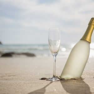 garrafa-de-champanhe-e-duas-tacas-na-areia_1252-511